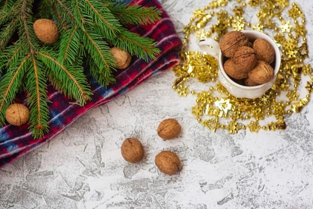 トウヒの緑の枝、赤い格子縞、クルミのカップの新年またはクリスマスの構成