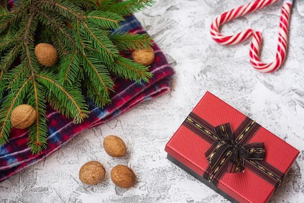 スプルースグリーンの枝、赤い格子縞、クルミ、ギフト、クリスマスロリポップの新年またはクリスマスの構成