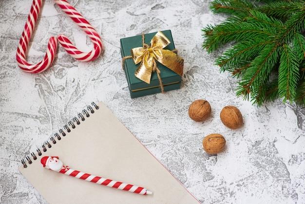 明るいテクスチャの背景にトウヒの緑の枝、クルミ、ギフト、ノートブック、クリスマスのロリポップの新年またはクリスマスの構成。フラットレイ、レイアウト、フレーム、コピースペース