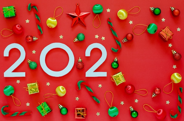 New year's ornament decorations with number of the year and empty copyspace on red . flat lay minimal holiday .
