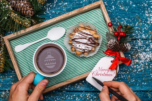 Новогоднее фото чая с игрушкой, торт на столе с еловой веткой, человек, пишущий пожелания на открытке