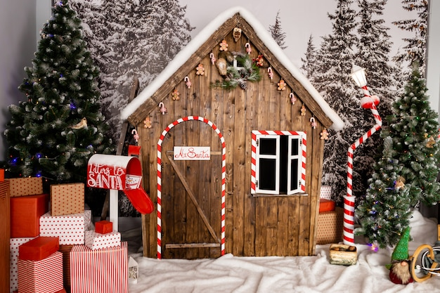 New year's photo zone with snow near a wooden toy house.