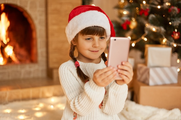 New year's portrait of little cute girl against by christmas tree and fireplace, child holding mobile phone, has video call and congratulating, somebody, wearing festive red hat.