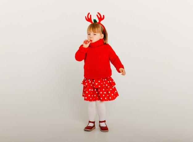 사슴 프레임과 흰색 배경에 빨간 스웨터에 어린 소녀의 새해 초상화.