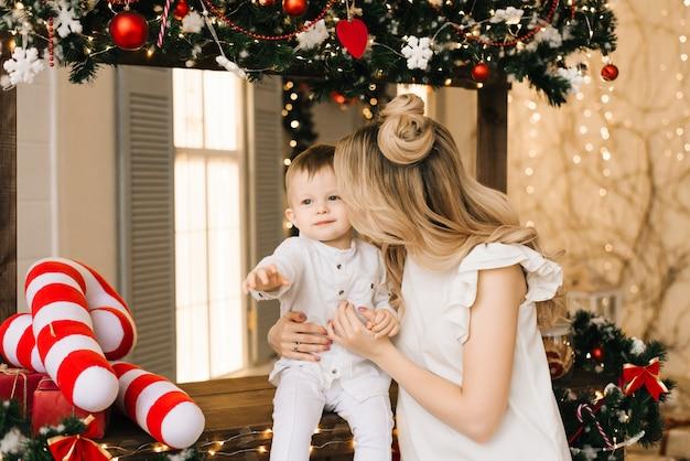 クリスマスバーを持つ若い息子を持つ若い魅力的な母親の新年の肖像画。新年とクリスマスのコンセプト
