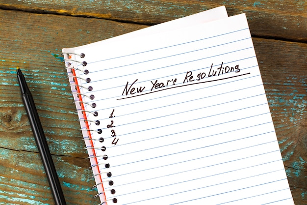 Новогодняя резолюция, написанная в блокноте и ручке. концепция новогодних резолюций.