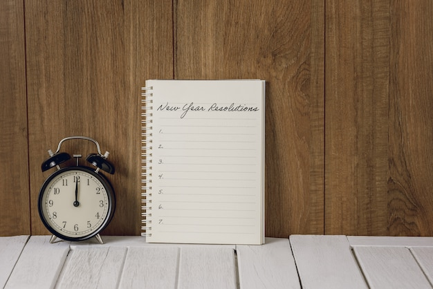 New year's resolutions list written on notebook with alarm clock