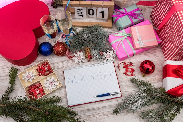 New year's resolutions in notepad with colorful balls and gift boxes on wooden table