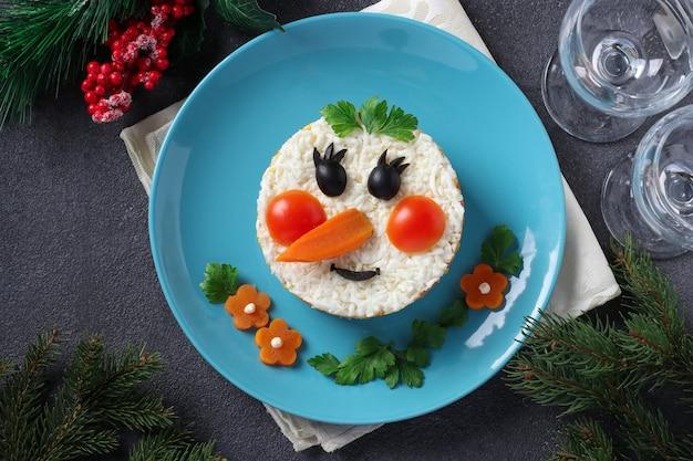 Новогодний салат в виде снеговика на синей тарелке на сером фоне. вид сверху