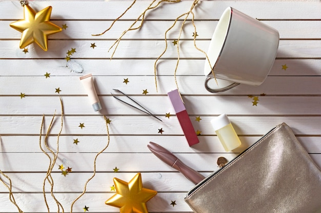New year's set of women's makeup cosmetics on wooden background with golden stars.