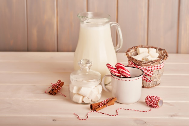 New year's sweets marshmallows, lollipops and milk on the table with gifts