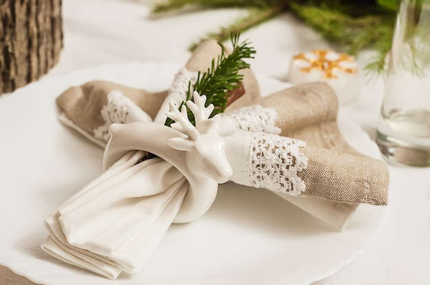 New year's table setting, holder for napkins in the form of a ceramic deer