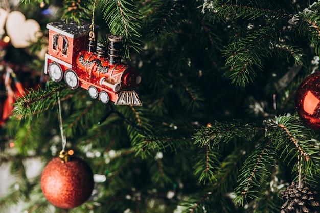 Новогодняя игрушка: висячий старый поезд и красные шары на елке. рождество и новый год.