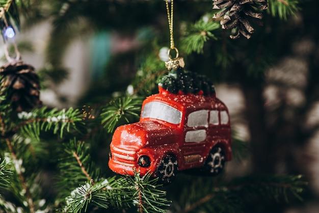 Новогодняя игрушка: висящий красный автомобиль и красные шарики на елке с размытым фоном