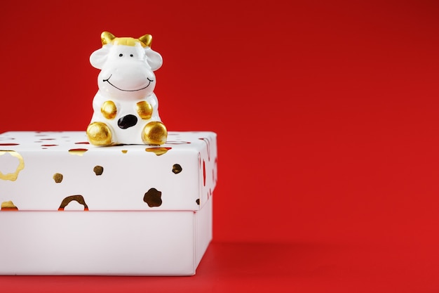 New year's toy of a cow on a box with a gift on a red background