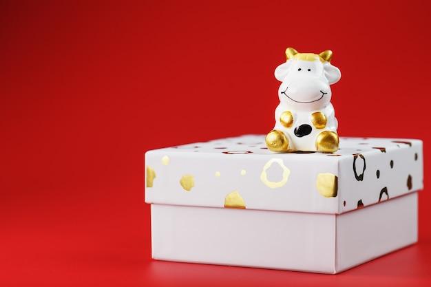 Новогодняя игрушка корова на коробке с подарком на красном фоне