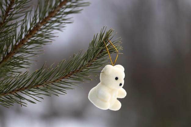 森の中のクリスマスツリーの枝に新年のおもちゃの白いテディベアがぶら下がっています。高品質の写真