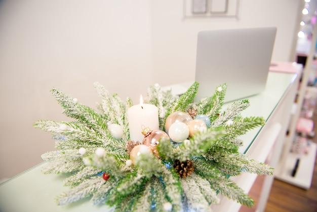 お正月の花輪とオフィスのデスクトップデコレーションとしての白いキャンドル。