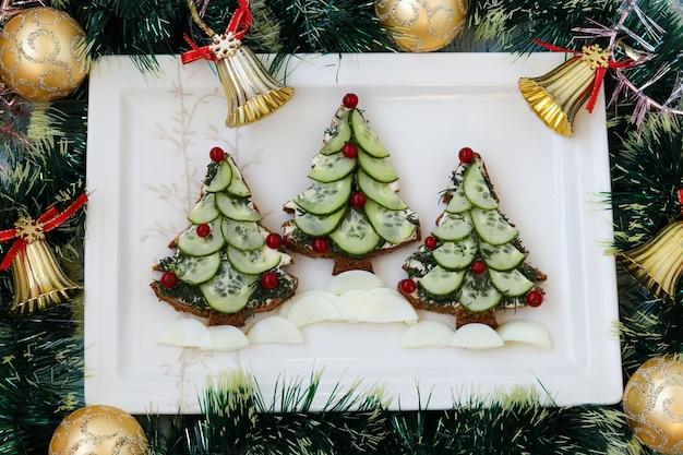 クリスマスツリーの形をした黒いパン、チーズ、きゅうりの新年のサンドイッチ、装飾されたベリー、白いプレートに配置、上面図