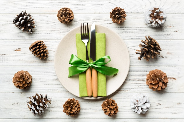 New year set of plate and utensil on wooden background. top view of holiday dinner decorated with pine cones. christmas time