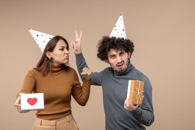 정서적 미친 충격을받은 젊은 부부와 함께 새해 촬영 새해 모자 화가 소녀 착용