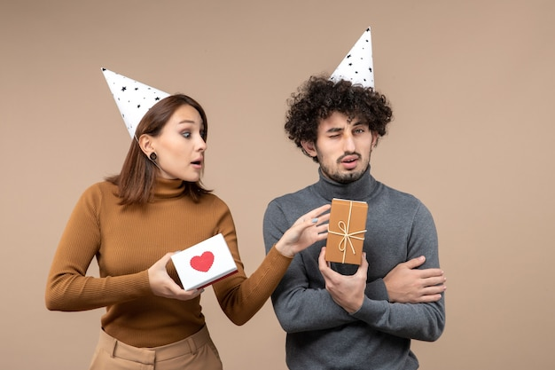 Le riprese di capodanno con la giovane coppia scioccata pazza emotiva indossano la ragazza curiosa del cappello del nuovo anno con il cuore