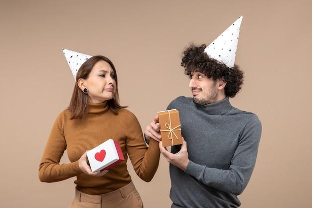 若いカップルがお互いを見つめながら新年の撮影は、心のある新年の帽子の酸っぱい顔の女の子を着用します