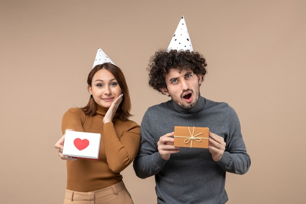 若いカップルと新年の撮影は、灰色のストックフォトに心と贈り物を指している新年の帽子の女の子を着用します。