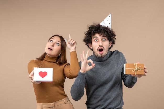 若いカップルと一緒に新年の撮影は、ハートを上に向けて新年の帽子の女の子とギフトを作る眼鏡のジェスチャーを持つ男を着用します