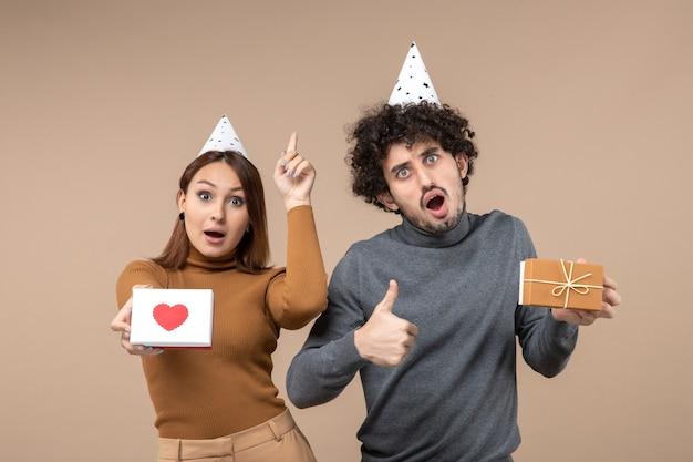 若いカップルとの新年の撮影は、ハートを上に向けた新年の帽子の女の子とギフトを作る男とokジェスチャーを着用します