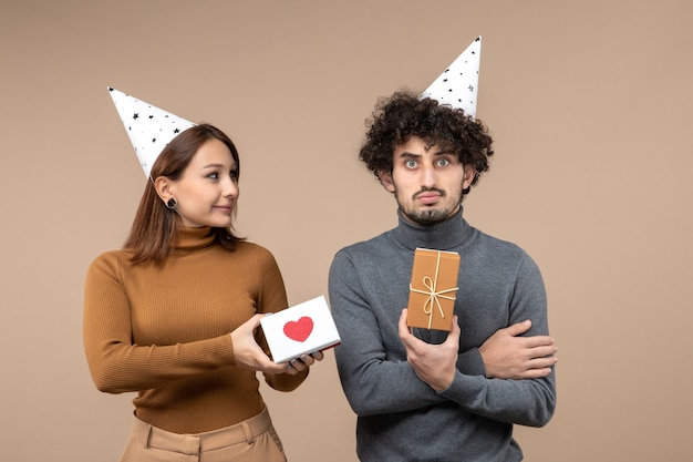 New year shooting with young couple wear new year hat romantic girl with heart and sad guy with gift on gray