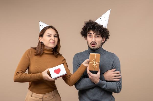 若いカップルとの新年の撮影は、心のある新年の帽子の酸っぱい顔の女の子と贈り物の混乱した男を着ています
