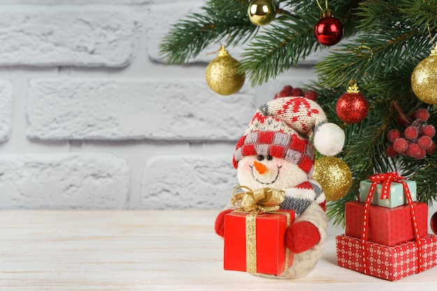 장식 된 크리스마스 트리 배경에 빨간색 선물 상자와 함께 새 해 눈사람