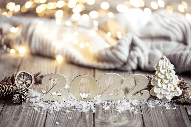 New year still life with decorative number of the coming year on a wooden surface against a blurred background.