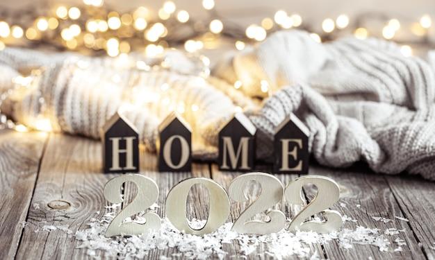 Новогодний натюрморт с декоративным числом наступающего года на деревянной поверхности с декоративными элементами на размытом фоне.