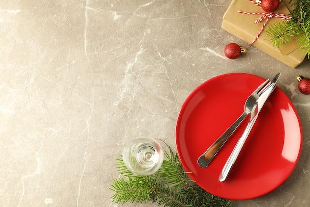 Сервировка новогоднего стола на сером текстурированном фоне.