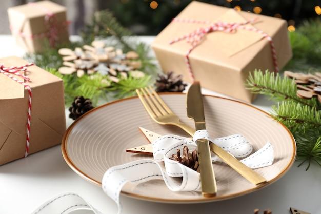 Сервировка новогоднего стола на белом столе.