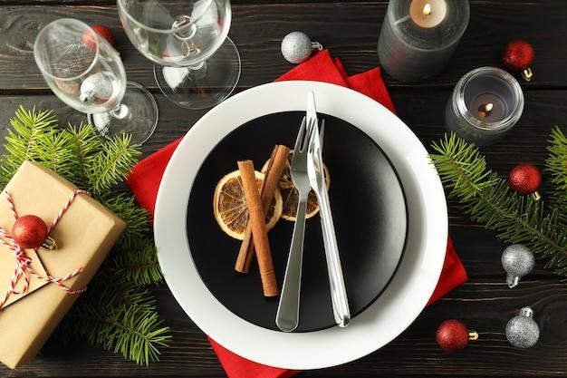Сервировка новогоднего стола на деревянном фоне.