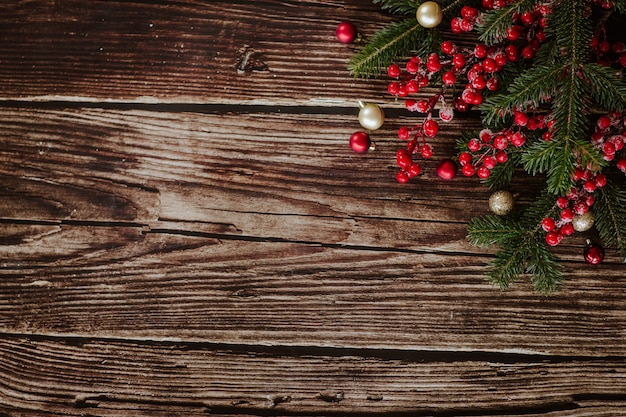 Новогодний шаблон с елочными украшениями, шарами и красными ягодами на деревянной текстурированной поверхности. вид сверху.