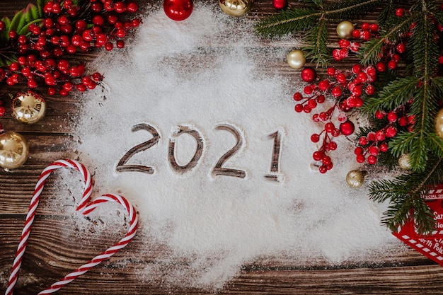 New year template with christmas tree decorations, balls, letter, sweets, flour and red berries on a wooden textured surface. view from above.