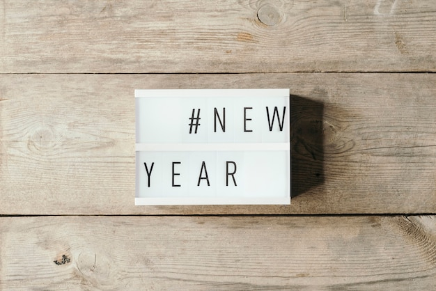 木製の背景を持つledパネルの新年のテキスト