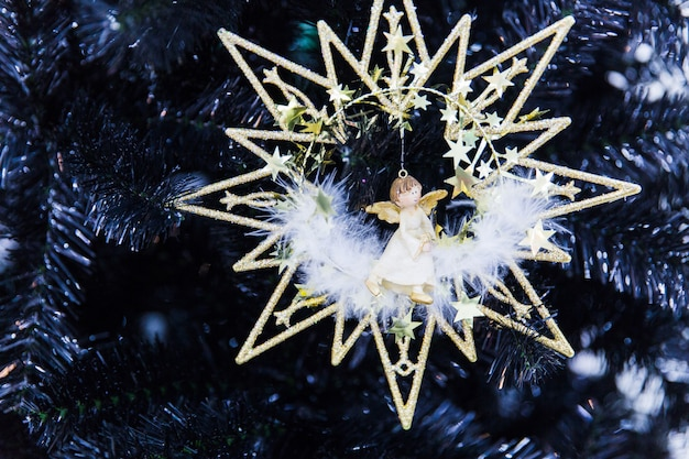 New year toy in the shape of star with angel on black christmas