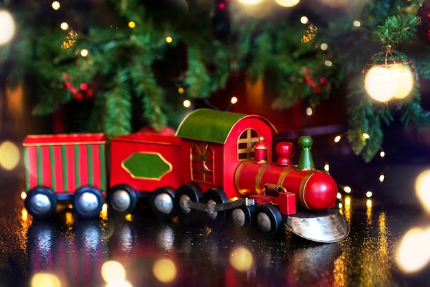 New year toy train at the christmas tree and lights