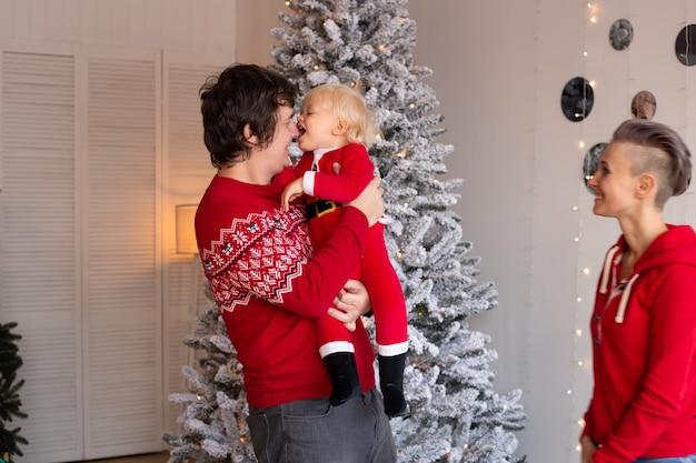 背景に新年のツリーとクリスマスプレゼント。家で幸せな家族のクリスマス。