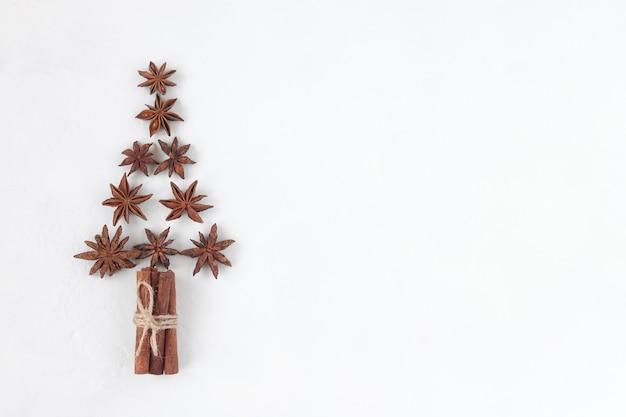 Новогодняя елка из звездчатого аниса и палочек корицы, белый фон, вид сверху, копия пространства, идея для рождественской открытки