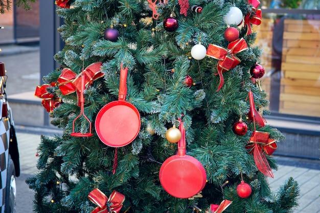 街の通りにあるお正月の木で、台所用品で飾られています。フライパンと泡立て器からのクリスマスデコレーション。珍しいクリスマスツリーのデザイン