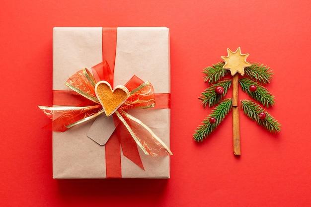 Новогодний винтажный подарок с красной лентой рядом с елкой ручной работы