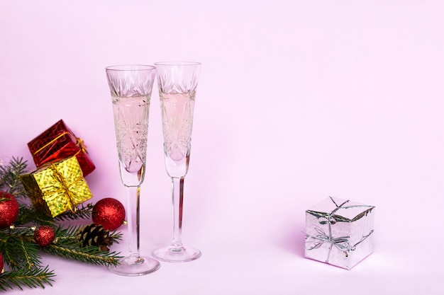 New year winter composition with two glasses champagne on pink background