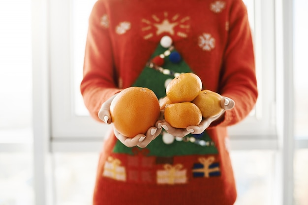 New year and winter concept. cropped shot of female in funny christmas sweater holding orange and tangerines, offering it to friend, standing near window. girl got ill and boyfriend brought vitamin c