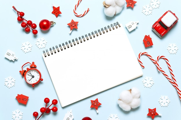 New year winter holiday xmas concept writing in notebook with gifts and decor on blue background